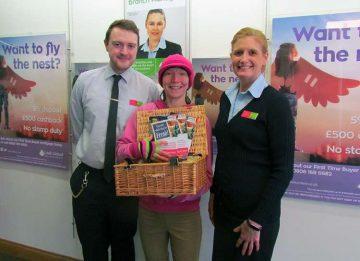 Julie Ann Birks receives her 'Totally Locally Leek' hamper prize from Leek United's Callum Gater and Bev Northcott.