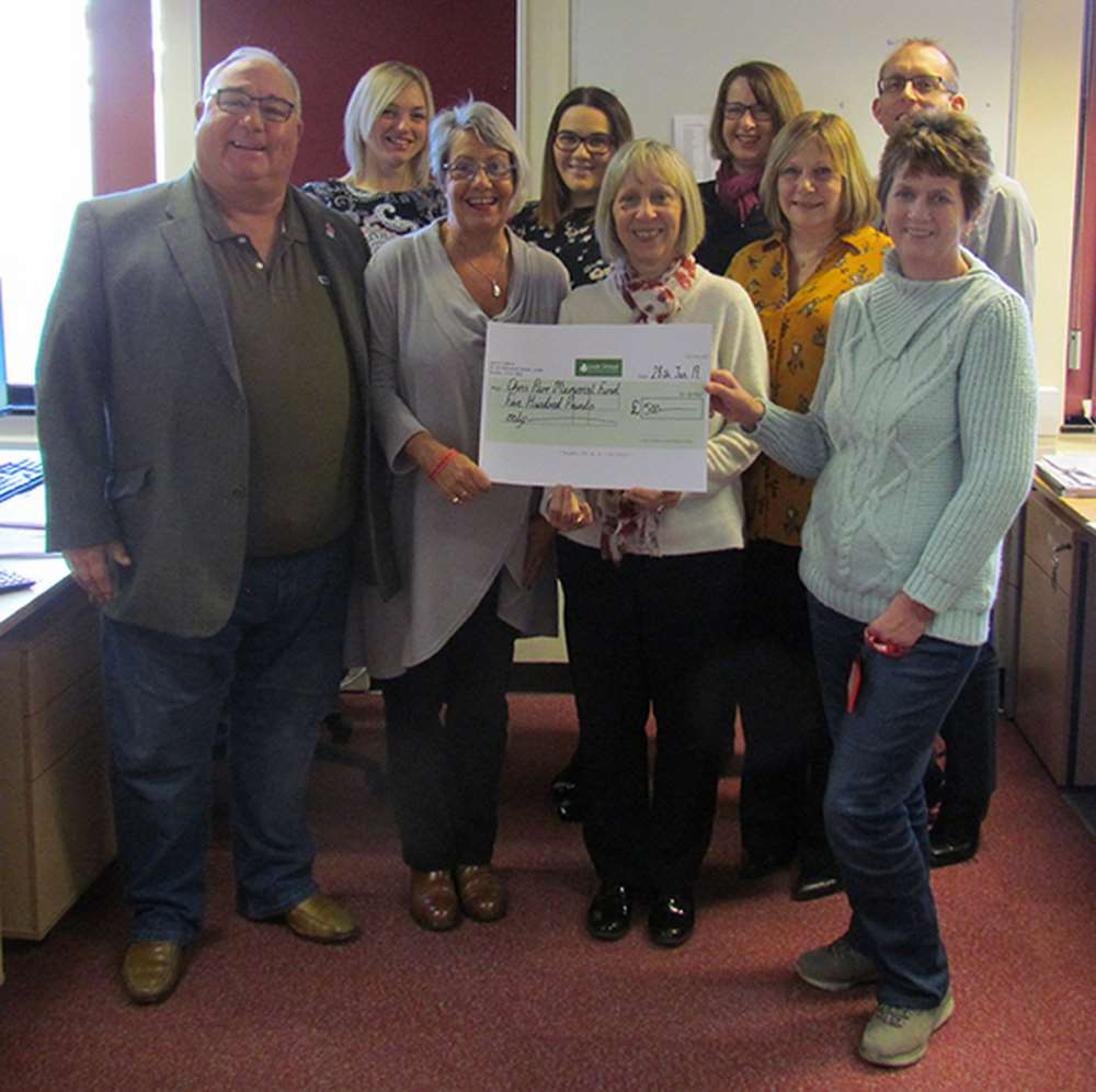 Martin and Dianne Parr (front row, left and second from left) receive the £500 cheque from members of Leek United's Mortgage Operations team.
