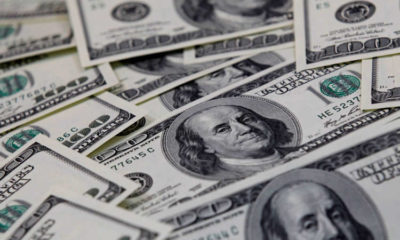 Dollar rises after U.S. data, but posts largest monthly fall since December 7